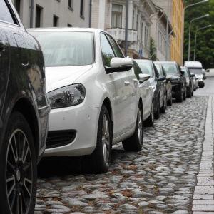 En rad av parkerade bilar längs en gata.