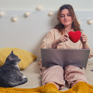Kvinna sitter på en säng med sin katt och håller i ett tyghjärta.