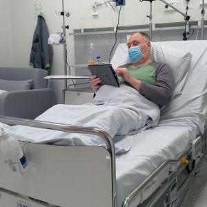 Heljo Hakulinen lukee tablettia sairaala Novan potilashuoneessa.