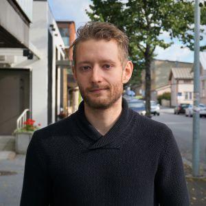 Man i svart tröja står på en trottoar.