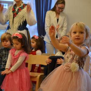 Finklädda barn dansar.