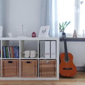 Bild på en bostad med en hylla och en gitarr.