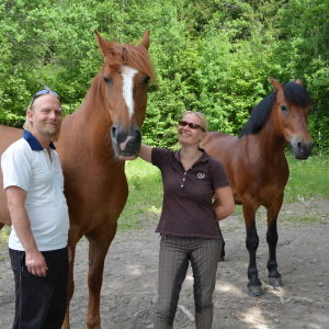 Björn Holmberg och Pia Kulla står tillsammans med två ståtliga, bruna hästar.