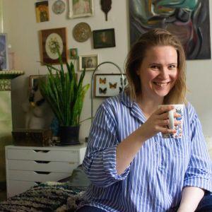 Outi Pyy juo teetä isosta mukista ja katsoo hymyillen kameraan. Hänellä on yllään sini-valko-raidallinen paita.