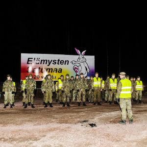 En grupp beväringar samlas i kvällsbelysning vid Nylandsgränsen.