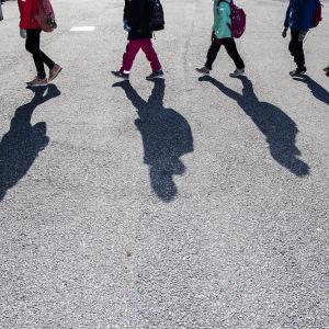 Skolelever går på rad, man ser mest skuggorna av dem.