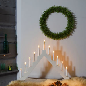 Ett julpyntat hörn i ett hem där en tunn tallriskrans hänger på en vit vägg, en stor adventsljusstake står tänd och några små lyktor lyser på sidan.