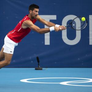 Novak Djokovic slår en boll i OS.