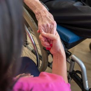 Skötare håller in en äldre människas hand.