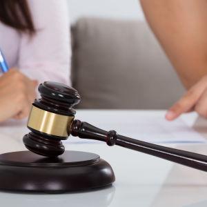 En klubba man använder för att klubba av beslut ligger på ett bord och i bakgrunden ser man händerna och lite av kroppen på två personer där den ena pekar på ett papper på ett bord och den andra håller i en penna.