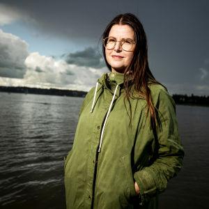 En kvinna med grön jacka och glasögon på en brygga.