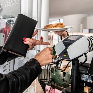 Nainen maksaa sirukortilla kahvilassa.