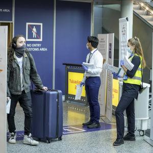 En resenär anländer till Helsingfors-Vanda flygplats och emottas av personal med infoblad.