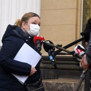 Krista Kiuru med munskydd ger intervju framför mikrofonerna på Ständerhusets trappa