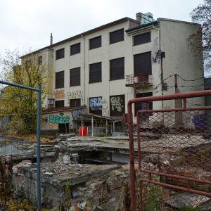 Et förfallet hus, framför ligger en massa tegelstenar, hål i marken och klotter på väggarna.