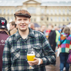 Niklas Backlund, festivalbesökare på Craft Beer Helsinki. Står med ett ölglas i vänstra handen och ser glad ut.