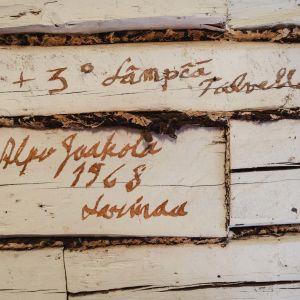 Valkoiseen seinään ruskealla kirjoitettu teksti: Plus kolme lämpä talvella, Alpo Jaakola, 1968, Loimaa