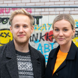 Simon Karlsson och Märta Westerlund poserar framför staket och graffitivägg på Yles gård.