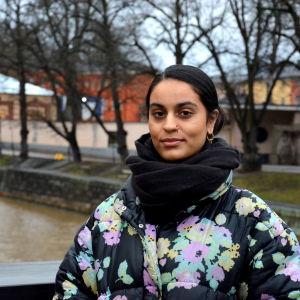 en kvinna med pakistanskt ursprung står på en bron invid aura å i höstväder iklädd svart tjock halsduk och blommig tjock jacka.