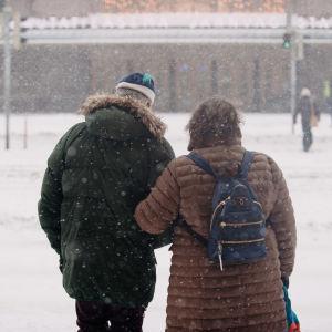 Pariskunta ylittämässä suojatietä Helsingin rautatientorin edessä.