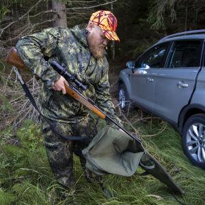 Metsästäjä Miro Oikarinen laittaa kivääriään suojapussiin autonsa vierellä metsässä.