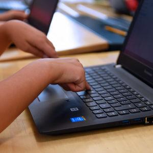 Barn händer som skriver på datorn