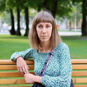 Kristina Huhtasalo är klädd i en grön tröja och sitter på en parkbänk.
