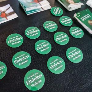 Keskustapuolueen kuntavaaliehdokasrintamerkkejä ja vaalimateriaalia pöydällä.