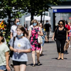Människor går på stan i Helsingfors i juni 2021. Många av dem bär munskydd.