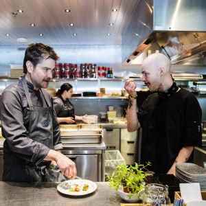 Två män står i ett kök och provsmakar mat.