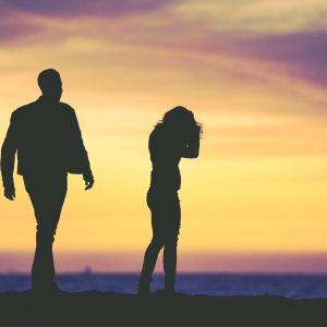 Mies ja nainen seisovat erillään auringonlaskussa.