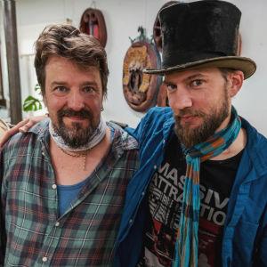 Två män, båda med skägg, den ena med svart sliten cylinderhatt, håller varandra om axlarna och ler in i kameran.