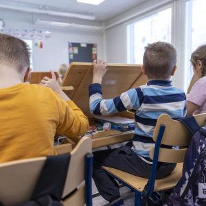 Barn som gräver fram saker ur sina pulpeter i skolan.
