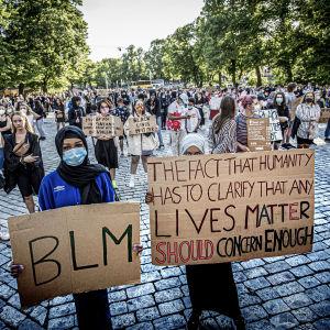 Två kvinnor iklädda hijab står med sina plakat framför en folksamling.