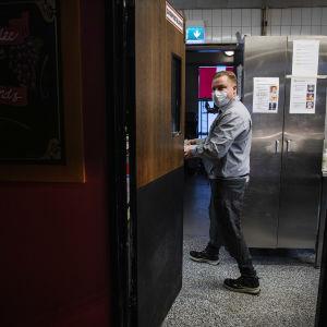 Kuvassa kasvomaskia käyttävä tarjoilija työskentelee ravintola Vltavassa lokakuussa 2020.