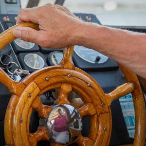 Miehen käsi pitää veneen ruorista kiinni.
