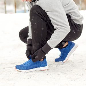 Person med låga skor och bar vrist i snön.