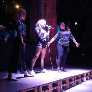 Tre unga kvinnor med blåvitrandiga tröjor sjunger på en stämningsfullt upplyst scen