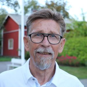 En man med glasögon står på en gård. I bakgrunden skymtar ett rött hus.