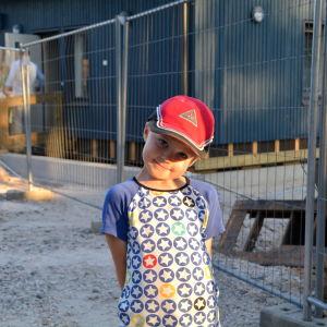 En ung pojke ler framför ett staket.