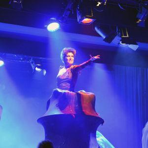 "En kvinna på scen som står inne i ett ""berg"" med den enda armen utsträckt mot publiken."