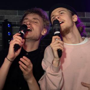 Olavi Tanttu ja Arttu Porkka laulavat karaokea yhdessä. Ilmeet ovat voimakkaasti lauluun eläytyvät.