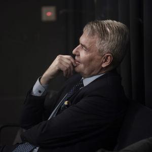 Pekka Haavisto sitter på en stol och tittar åt sidan.