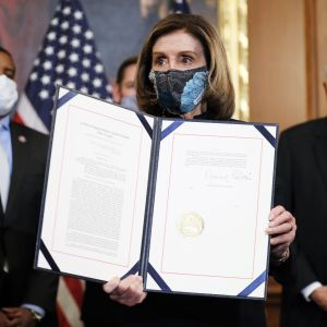Nancy Pelosi pitää käsissään asiakirjaa ja esittelee sitä kameroille. Hänellä on kasvoillaan maski. Taustalla näkyy kolme miestä tummissa puvuissa ja maskit kasvoilla. Huoneen seinän vierellä on Yhdysvaltain lippuja.