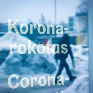 Koronarokotuspaikan lasiovesta heijastuu kävelevän ihmisen hahmo. Ovessa lukee teksti koronarokotus.