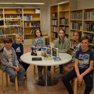 Dag Bahér, Casper Malmsten, Birna Hampf, Lovisa Lindbom, Alma Lindholm. Rudi Viljanen sitter vid ett bord i biblioteket i Degerby skola.