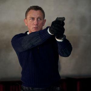 James Bond riktar sitt vapen mot någon snett utanför bild.
