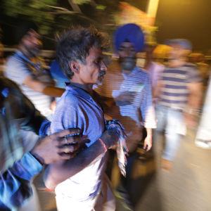 En skadad man hjälps till en ambulans efter en tågolycka i Amritsar, norra Indien.