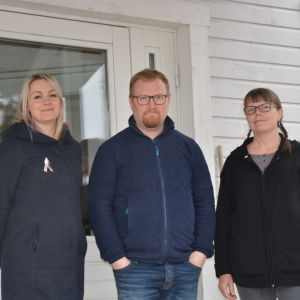 Tre personer står vid husvägg.
