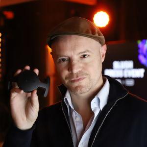 En man som håller en liten plastdisk som kan fästas i en mössa.